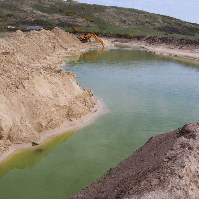 A green lagoon in a pit of sand