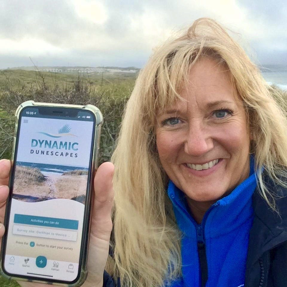 A happy blonde female volunteer smiles at the camera holding her phone open towards the camera, open on the app home screen
