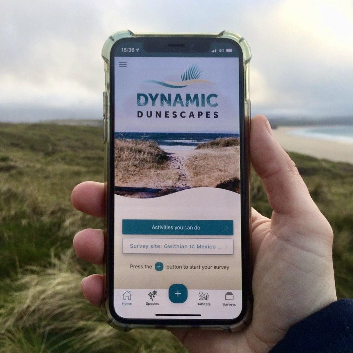 A hand holds a smartphone which is open on the homepage of the app, with the coast in the background